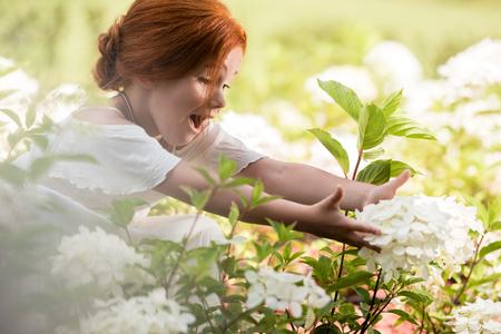 redhead girl in flower bed Фото со стока