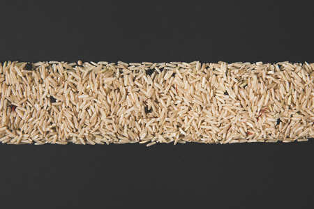 top view of stripe of raw rice isolated on black