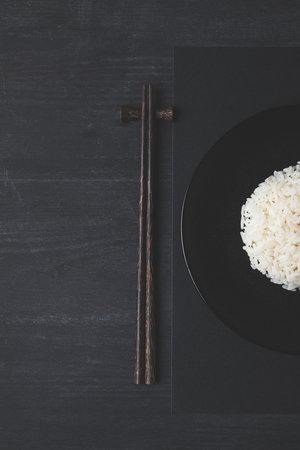 top view of rice and chopsticks on black table