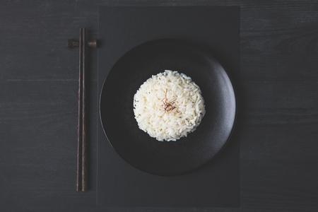 검은 테이블에 맛있는 쌀과 젓가락의 상위 뷰