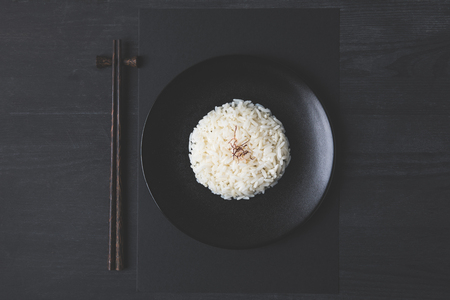 top view of tasty rice and chopsticks on black table