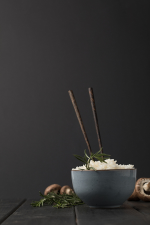 bowl of tasty rice with chopsticks and mushrooms on black tabletop Stok Fotoğraf