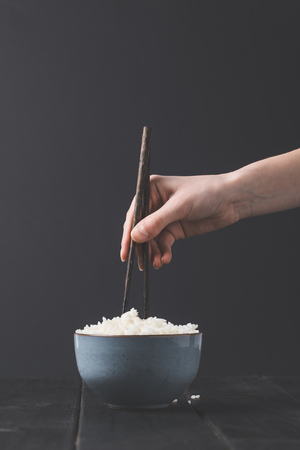 cropped shot of woman taking rice from bowl with chopsticks Stok Fotoğraf