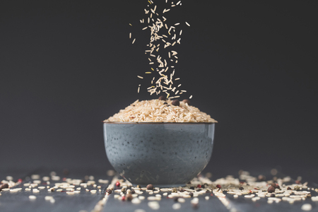 side view of rice spilling into bowl on black table