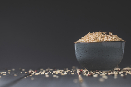 bowl of raw rice on black table with copy space