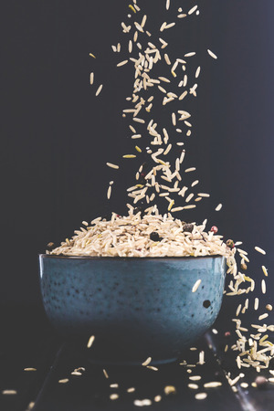 close-up shot of rice spilling into bowl on black table