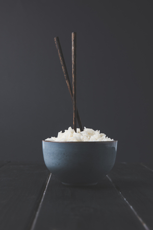 bowl of freshly cooked rice with chopsticks on black table Stok Fotoğraf