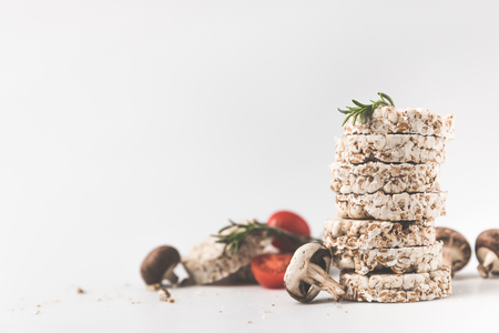 stack of rice cakes with mushrooms and tomatoes on white surface