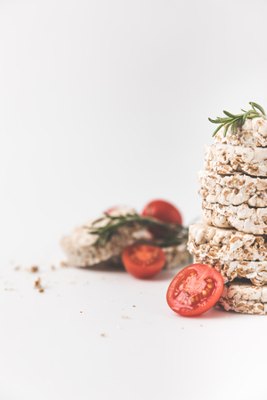close-up shot of stack of rice cakes with rosemary and tomatoes on white tabletop