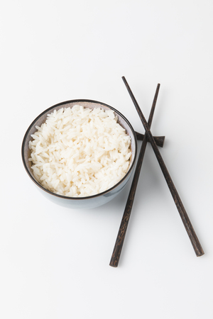 bowl of freshly cooked rice with chopsticks on white tabletop