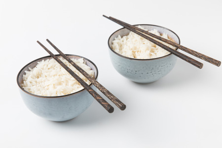 bowls of tasty rice with chopsticks on white surface Stok Fotoğraf