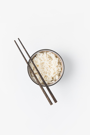top view of bowl of freshly cooked rice with chopsticks isolated on white