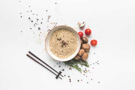 flat lay composition of raw rice in bowl with mushrooms and tomatoes on white surface with chopsticks Stok Fotoğraf