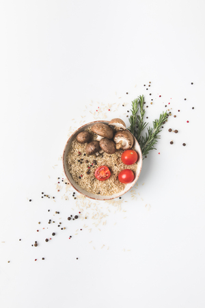 flat lay composition of raw rice in bowl with mushrooms and tomatoes on white tabletop