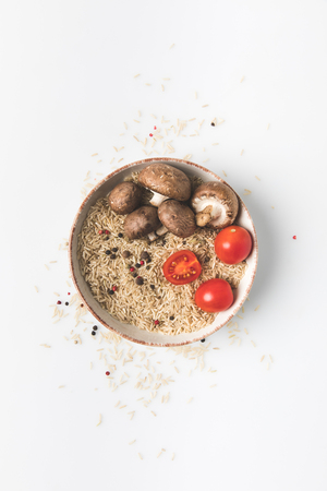 top view of raw rice in bowl with mushrooms and tomatoes on white surface with spilled rice and spices around Stock Photo