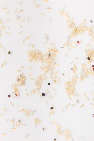 top view of spilled raw rice with peppercorns on white surface Stock Photo