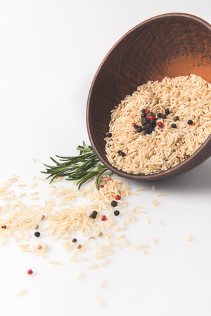 close-up shot of raw rice and spices spilling out bowl on white surface Stock fotó