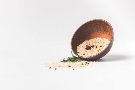 白い表面にボウルをこぼした生の米とスパイス