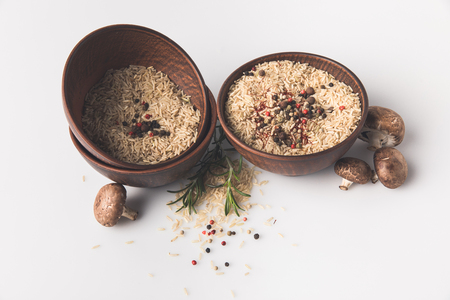 bowls of raw rice with spices and mushrooms on white tabletop Stock Photo