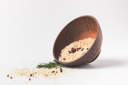 raw rice and peppercorns spilling out bowl on white surface Stock fotó