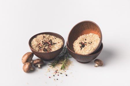 bowls of raw rice with spices and mushrooms on white surface Stock Photo