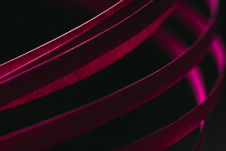 close up view of crimson quilling striped paper on black