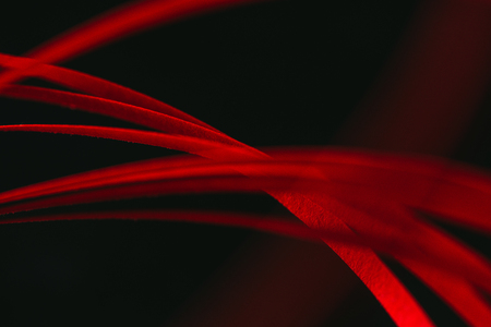 close up view of red quilling striped paper on black  Stock Photo