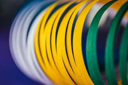 close up of white, green and yellow quilling paper curves on blue Stock Photo