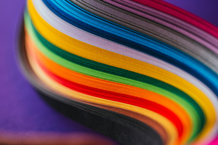 close up of colored bright quilling paper curves on purple