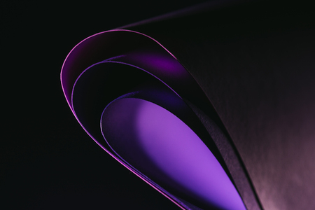 arcs of warping purple paper on black Reklamní fotografie - 94393055
