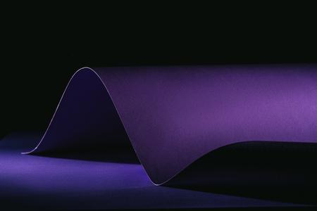 warping purple paper on purple surface on black