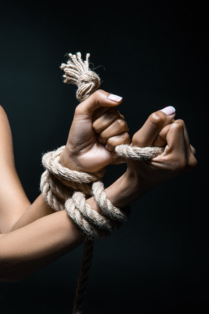 cropped shot of female hands bound with rope isolated on black