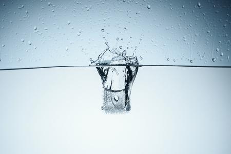 ice cube splashing in water, isolated on white Stock Photo