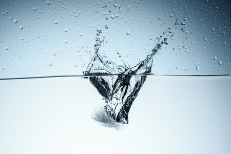 ice cube splashing in water with drops, isolated on white