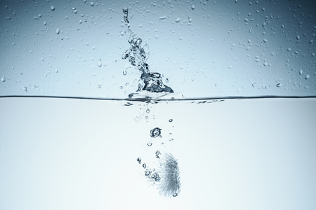 ice cube in water with splash, isolated on white Stock Photo