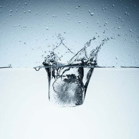 ice cube in water with splash and drops Stock Photo