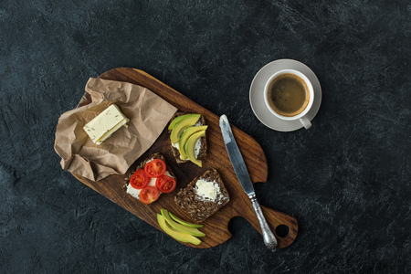 flat lay with snacks for healthy breakfast and cup of coffee on wooden cutting board on dark tabletop