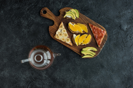 flat lay with snacks for healthy breakfast and teapot on wooden cutting board on dark tabletop
