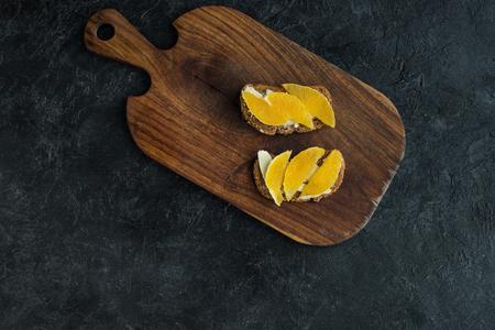 bovenaanzicht van snacks met stukjes sinaasappel voor het ontbijt op snijplank op donkere ondergrond