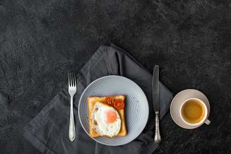 flat lay with cup of coffee and toast with fried egg and cherry tomatoes for breakfast on dark surface 스톡 콘텐츠