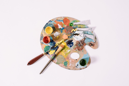 top view of palette with colorful paints isolated on grey