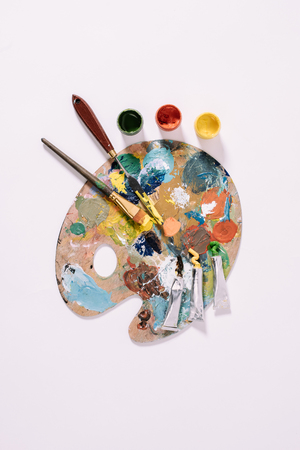 top view of palette with colorful paints and paint brushes isolated on grey
