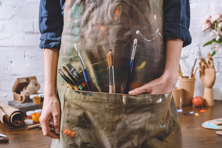 cropped image of artist with brushes and hand in apron pocket Imagens