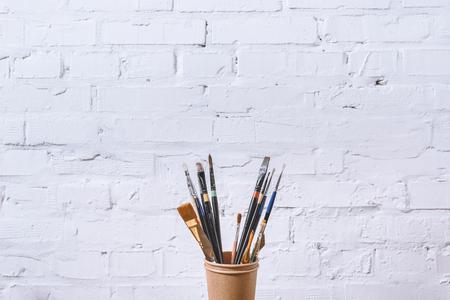 흰 벽에 종이 컵에 페인트 브러시