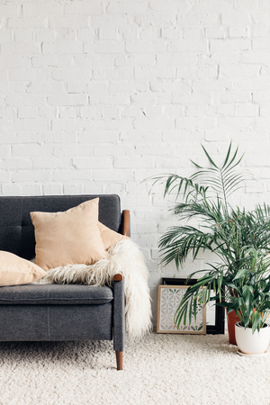 comfy couch with flowerpots in white living room interior with brick wall