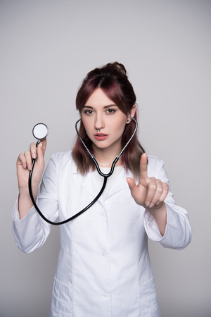 young female doctor holding stethoscope