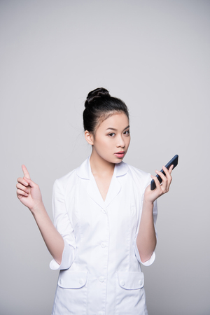 Young nurse holding smartphone