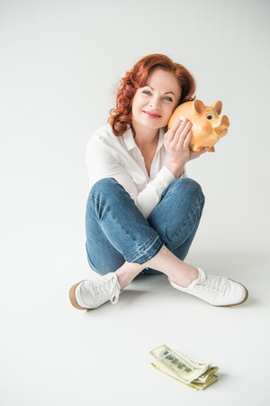 woman with dollars and piggy bank