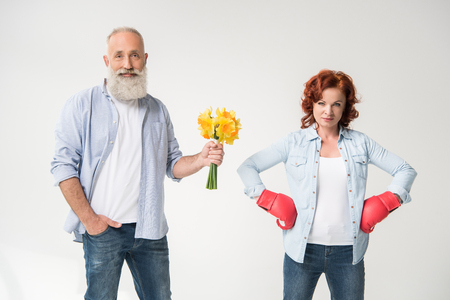 woman in boxing gloves and husband with bouquet Stock Photo