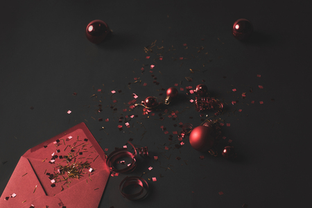 Christmas balls, confetti and envelope on black isolated background